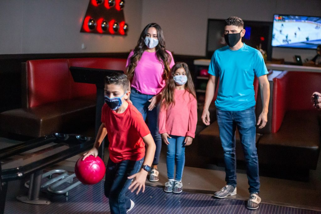 family bowling with masks